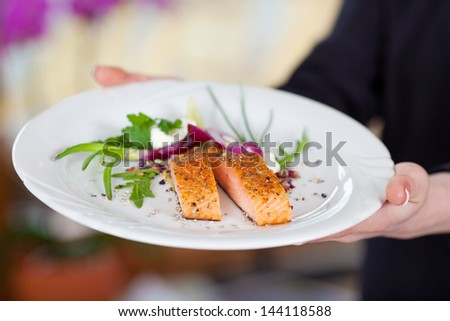 Cropped image of waitress displaying salmon dish in restaurant - stock photo