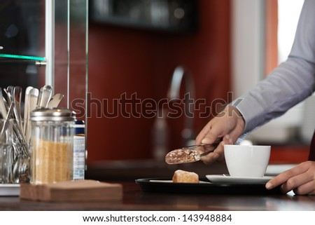 Cropped image of waitress keeping biscuit in tray at coffee shop counter