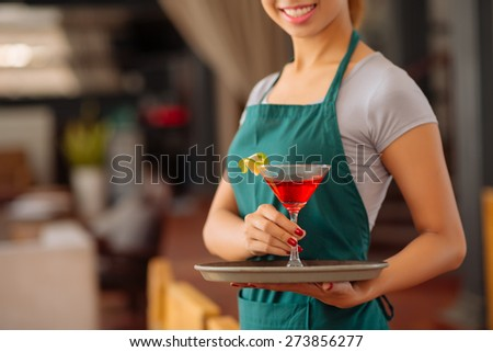 Cropped image of waitress serving red tropical cocktail