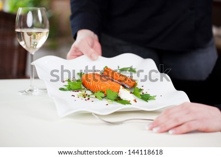 Cropped image of waitress serving salmon dish garnished with parsley at restaurant table - stock photo