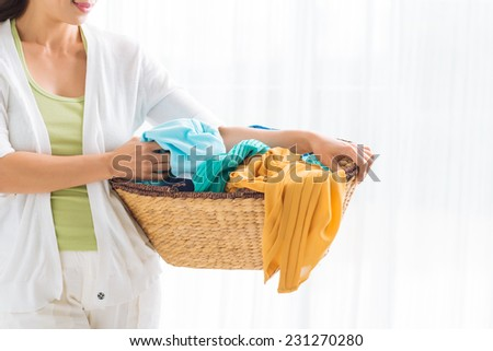 Cropped image of woman holding a laundry basket full of clothes - stock photo