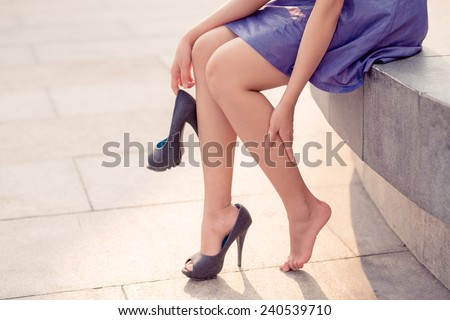 Cropped image of woman in high heels massaging her tired legs - stock photo