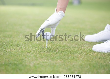 Cropped image of woman placing ball on golf tee - stock photo