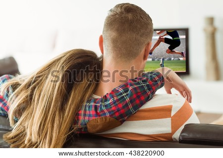 cropped image of woman practicing show jumping against cute couple relaxing on couch - stock photo