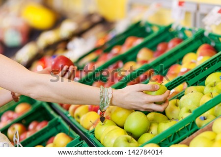 Cropped image of woman's hands choosing apples in grocery store - stock photo