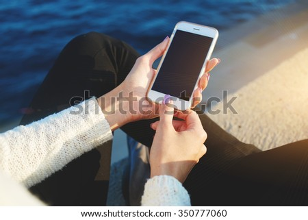 Cropped image of woman's hands holding smart phone with empty copy space screen for your text message or information content, hipster girl using cell telephone while relaxing in the fresh air near sea - stock photo