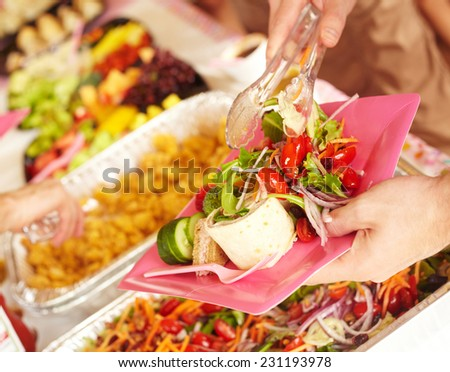 Cropped image of woman serving vegetable salad for herself at birthday party - stock photo