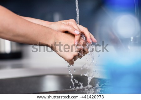 Cropped image of woman washing hands in kitchen at home