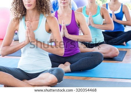 Cropped image of women doing easy pose with hands together in fitness studio - stock photo