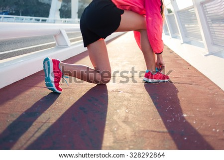 Cropped image of young athletic woman tying the laces on running shoes while taking break between physical exercise outside, fit woman tie shoelaces while standing on a road while jogging in summer  - stock photo