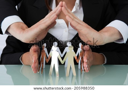 Cropped image of young business people sheltering team of paper people at office desk - stock photo