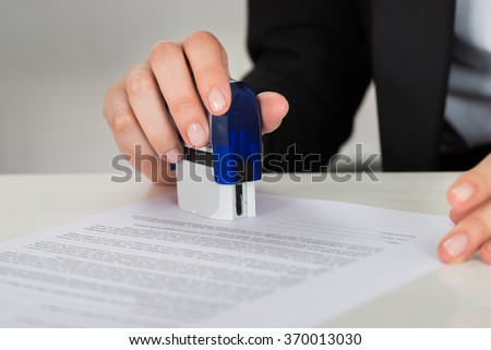 Cropped image of young businesswoman stamping contract document at office desk - stock photo