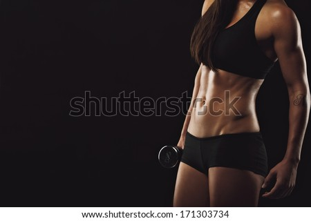 Cropped image of young female bodybuilder holding dumbbell against black background with copyspace. Fitness woman exercises with weights. Muscular body with perfect abs. - stock photo