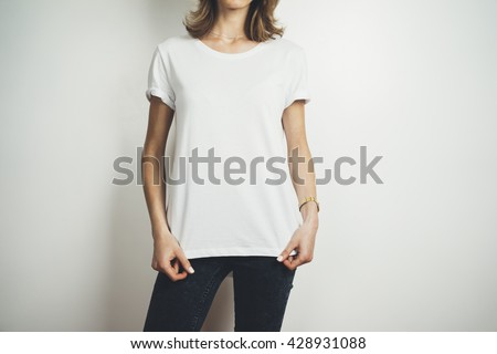 Cropped image of young hipster girl wearing blank white t-shirt and black jeans, mock-up of blank white t-shirt, white background