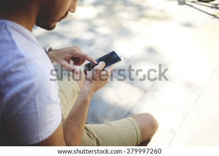 Cropped image of young man chatting on mobile phone with blank copy space screen for your advertising text message or content, bearded male viewing photos on cell telephone during free time outdoors - stock photo