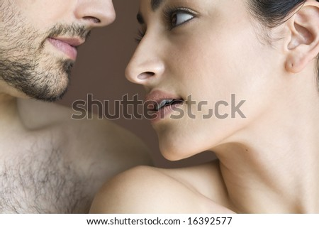 Cropped image of young man staring into the face of young woman