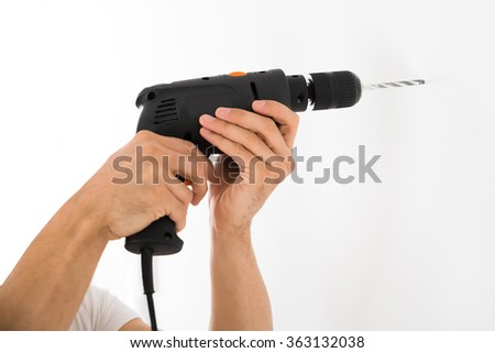 Cropped image of young man using power drill on white wall at home - stock photo