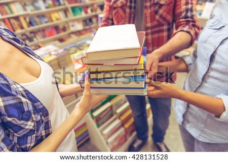 Cropped image of young students holding a pile of books while standing in the book shop - stock photo