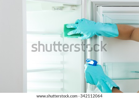 Cropped image of young woman cleaning refrigerator with sponge and spray at home - stock photo