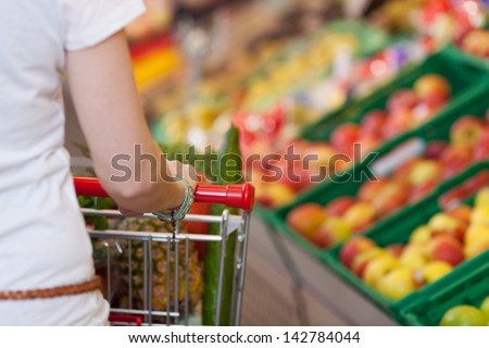 Cropped image of young woman pushing shopping cart in grocery store - stock photo