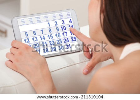 Cropped image of young woman using calendar on digital tablet at home - stock photo