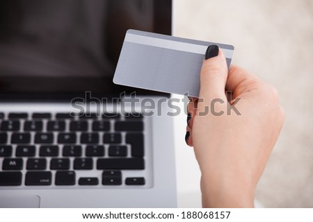Cropped image of young woman using credit card and laptop to shop online