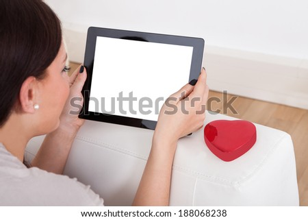 Cropped image of young woman using digital tablet for online dating - stock photo