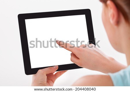 Cropped image of young woman using digital tablet over white background - stock photo
