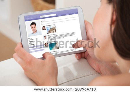 Cropped image of young woman using digital tablet to chat on social site while relaxing at home - stock photo