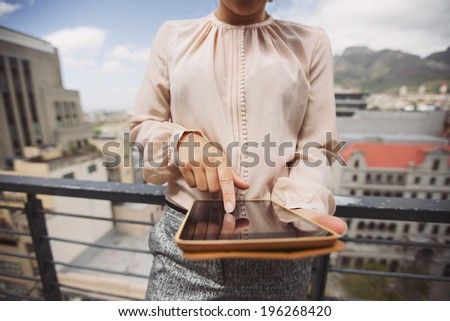 Cropped image of young woman working on tablet PC. Close up image of female standing on balcony using digital tablet. - stock photo