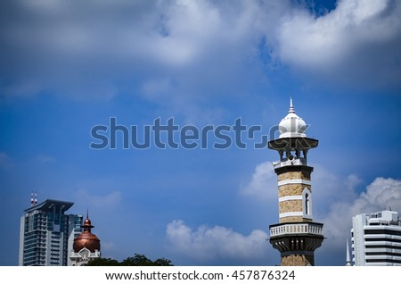 cropped image one of the Jamek Mosque minaret located in Kuala Lumpur, Malaysia over blue sky background at sunny day - stock photo