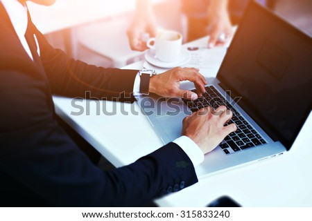 Cropped image view of man's hands in elegant suit keyboarding on laptop computer with blank copy space screen for your advertising content or text message, man working on net-book in a cafe, flare sun - stock photo