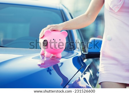 Cropped image woman customer, agent and new car, pink piggy bank key on hood isolated outside outdoors. Dealership offering credit line, finance services. Lease, automobile purchase, financing concept - stock photo