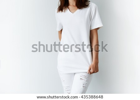Cropped isolated shot of young female model in trendy ripped denim pants stretching her blank T-shirt, holding a hand behind her back. Student girl trying on new clothes before going out for a walk - stock photo