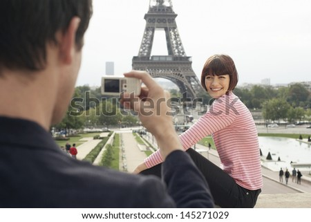 Cropped man photographing woman in front of Eiffel Tower