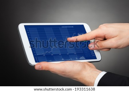 Cropped of businessman analyzing graphs on digital tablet against black background - stock photo