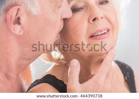 Cropped picture of a senior man about to kiss his wife on her cheek
