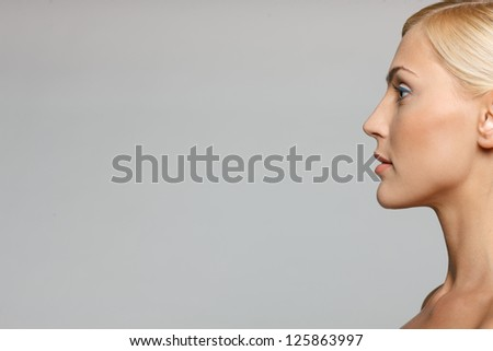 Cropped picture of side view closeup of beautiful blond woman looking forward over gray background