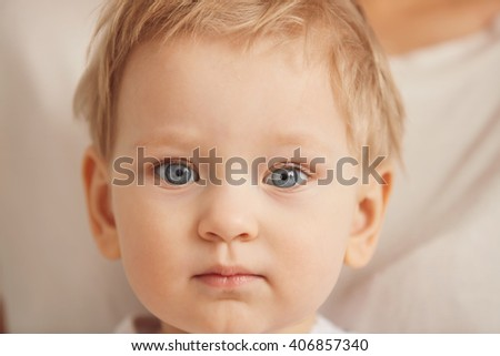 Cropped portrait of a lovely kid looking at the camera. Close-up image of a sweet toddler with blue eyes and blonde hair. Healthy childhood, perfect Caucasian infant, innocent concept