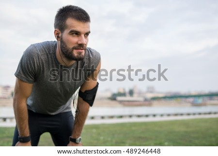 Cropped portrait of a young man catching a breather from exercise outdoors. Fit young male athlete stopping for rest while jogging along the river.