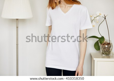 Cropped portrait of beautiful young woman with red hair and freckles looking away while standing against gray concrete wall background in home interior, wearing blank white T-shirt and black jeans  - stock photo