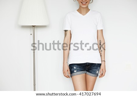 Cropped portrait of cute Caucasian teenage redhead girl posing against white concrete wall. Close up of happy attractive young woman in blank white T-shirt for your text message or advertising content - stock photo