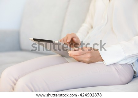 Cropped portrait of female freelancer working on digital tablet indoor. Young woman reading e-book or online magazine on electronic device while resting at home after hard working day in the office - stock photo
