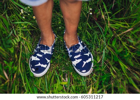 Cropped portrait of kids legs, walking on the summer wildflower's field. Summer concept.