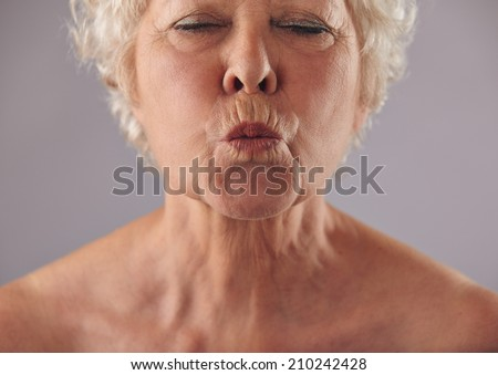 Cropped portrait of senior woman puckering lips. Mature female grimacing against grey background - stock photo
