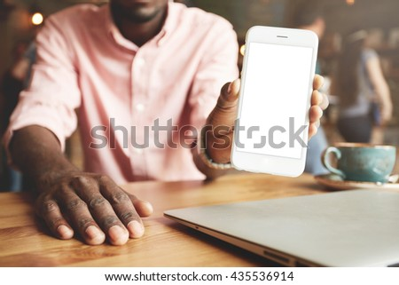 Cropped portrait of successful African American businessman in shirt, showing blank copy screen cell phone for your information or advertisement, having cappuccino during lunch break. Selective focus - stock photo