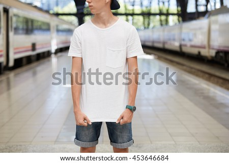 Cropped portrait of teenage boy wearing denim shorts and blank white T-shirt with copy space for your text or promotional content, posing against urban background, looking away, pulling T-shirt down - stock photo