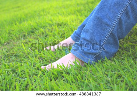 Cropped portrait of young girl with feet of lonely human sitting alone while resting on the grass. Selective focus on the front leg