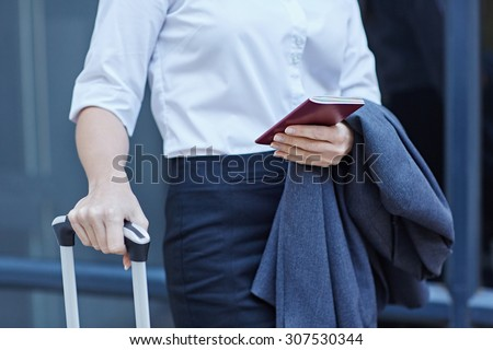 Cropped shot of a businesswoman with luggage and her passport - stock photo
