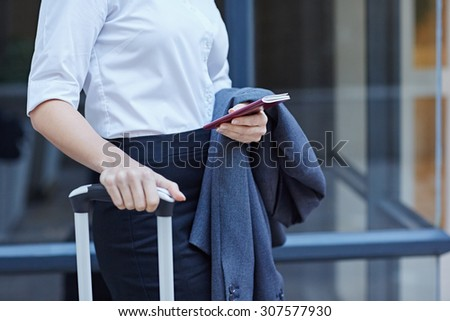 Cropped shot of a businesswoman with luggage and her passport on the airport - stock photo